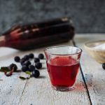 How to make sloe gin - a glass of sloe gin with sloes scattered on the table behind it