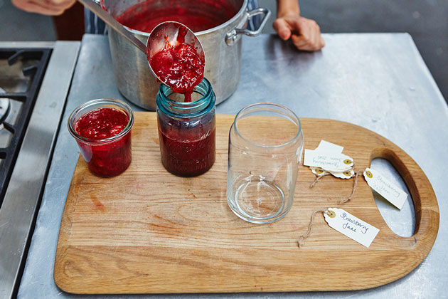 make jam - being spooned into mason jars