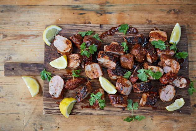 pork marinaded on a chopping board with herbs and lemon slices