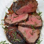 slices of steak with marinade on top and rosemary