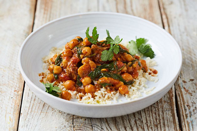 lamb and chickpea curry on rice with herbs on top