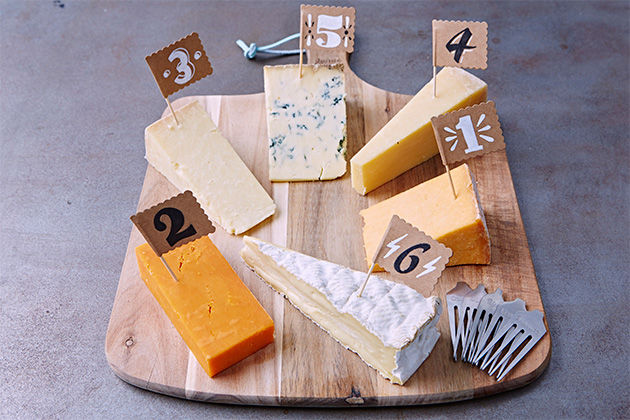 an assortment of cheese on a board