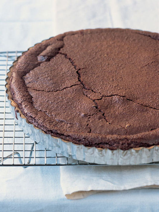 baked chocolate tart in a foil tray on a cooling rack
