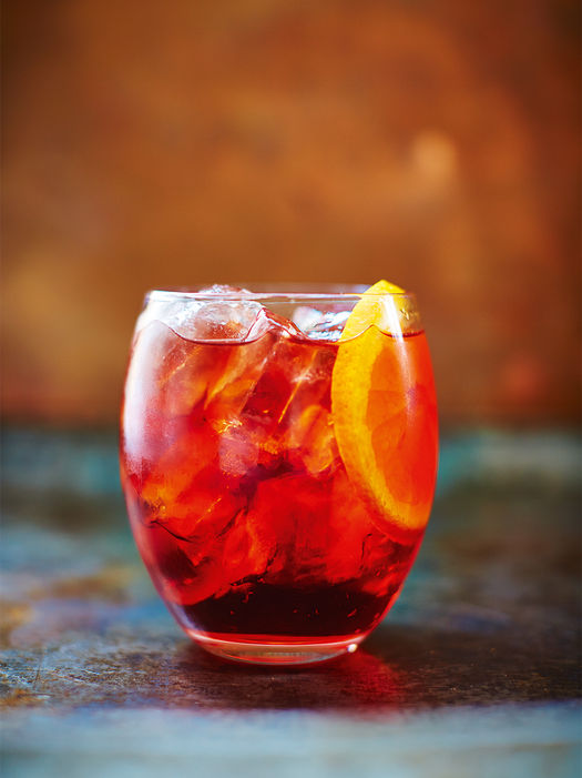 pink pepper negroni drink with a slice of grapefruit in