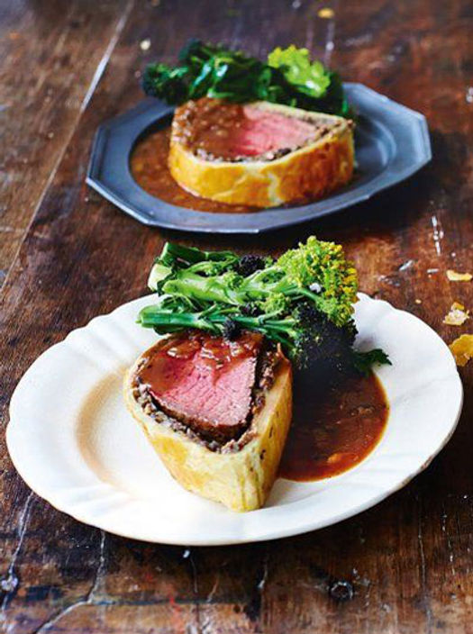 beef wellington with gravy and salad leaves