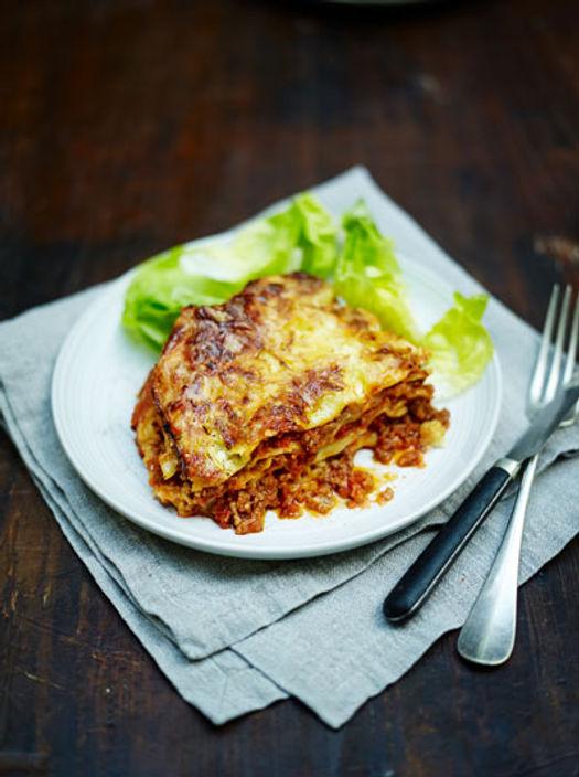 lasagne on a plate with salad on the side
