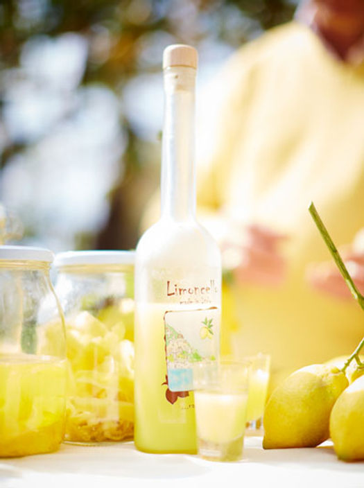 bottle of limoncello next to shot glasses and lemons