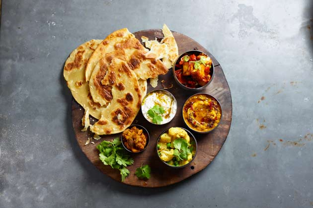 A wooden board with small pots of thali and parathas