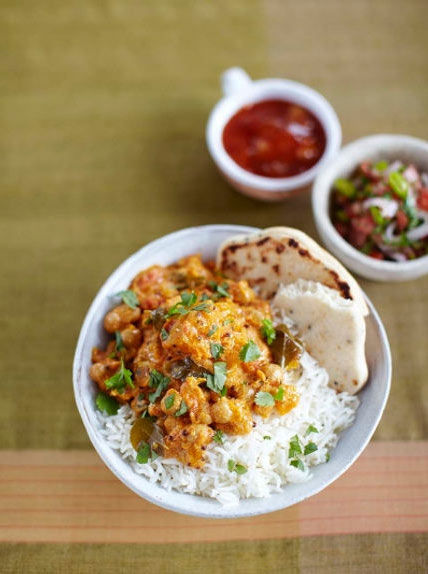 Bowl of chickpea and coconut burry with rice and chutney on the side