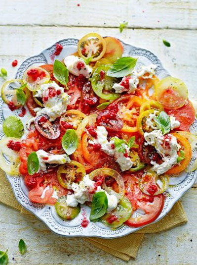 Plate of sliced red, green and yellow tomatoes sprinkled with basil