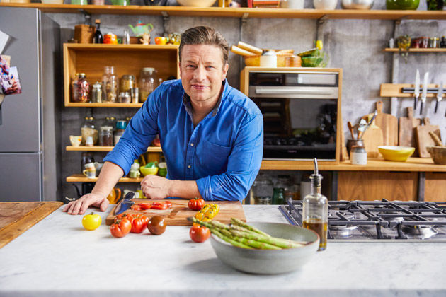 Jamie wearing a blue shirt, leaning on the kitchen counter with chopped tomatoes and asparagus in front of him