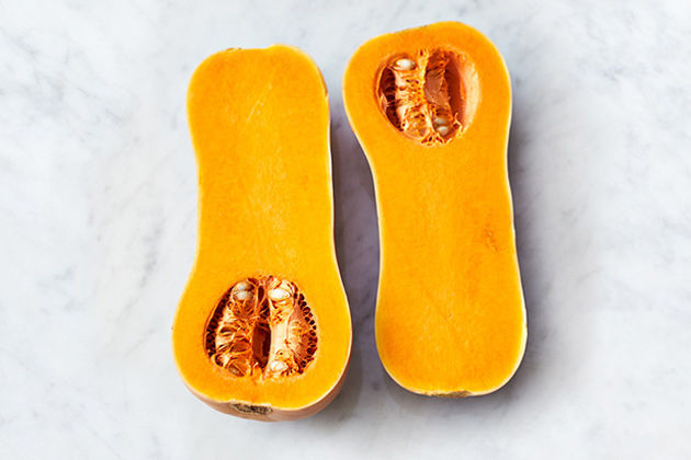 Butternut squash cut in half on a marble table