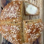Tin can soda bread recipe with a piece cut out and buttered