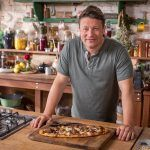 Jamie standing in the kitchen in front of a sausage pizza, a perfect freezer-friendly meal