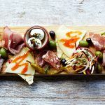 wooden board with a selection of cheeses, olives, hams and eggs on it