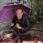 gennaro contaldo cooking in the rain under an umbrella