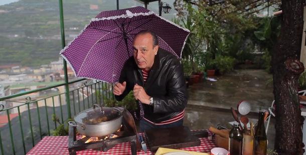 gennaro contaldo cooking in the rain under an umbrella