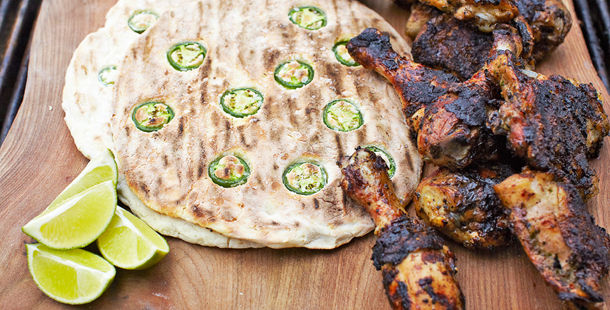 jalapeno flatbread with marinated, grilled chicken and lime slices on the side