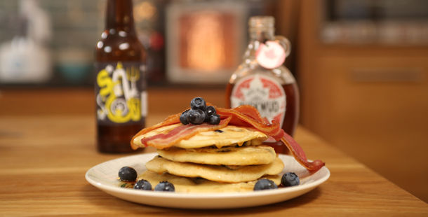 blueberry pancakes stacked with bacon and syrup on top