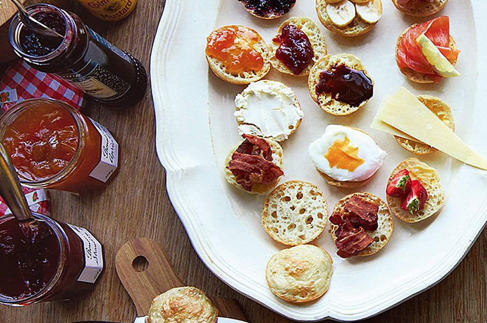 crumpets with jam, bacon, eggs, fruit and salmon on top