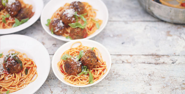 spaghetti in tomato sauce with meatballs and parmesan on top