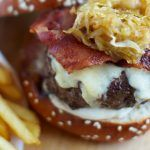 beef burger with melted cheese on top, bacon and onions with chips on the side