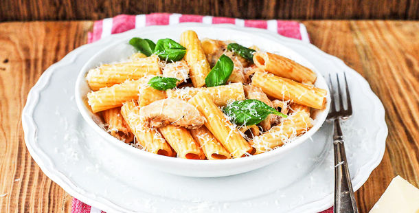pasta tubes with chicken cheese and herbs on top