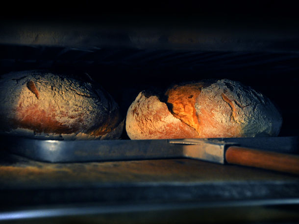 bread being freshly baked in stone oven