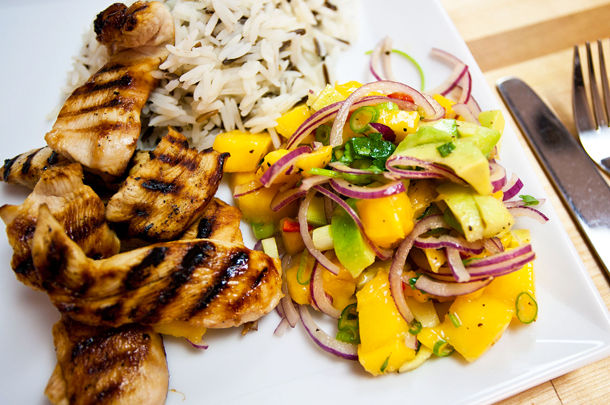 grilled chicken with rice and vegetables on the side