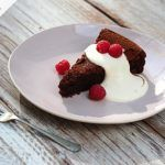 flourless chocolate cake slice with cream and raspberries on top