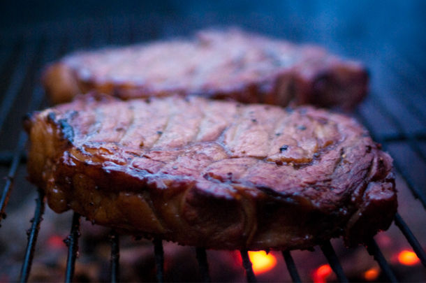 steak being grilled on a fire