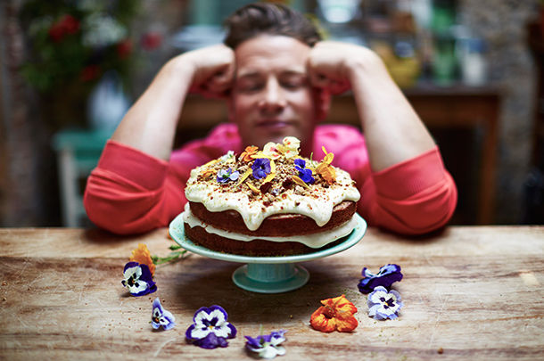 cake with buttercream icing and edible flowers on top and surrounding it with Jamie in the background