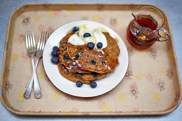 vegan pancakes with blueberries, syrup and cream on top