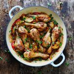 chicken legs roasted in a pan with lemon wedges and herbs