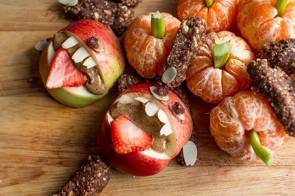 Healthy Halloween treats with apples and strawberries looking like monsters