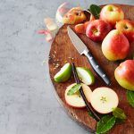 apples and pears being sliced on a chopping board