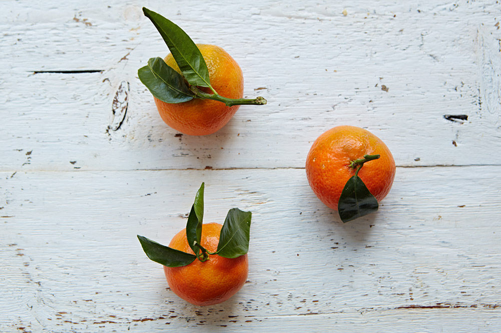 3 clementines with the leaves still on them