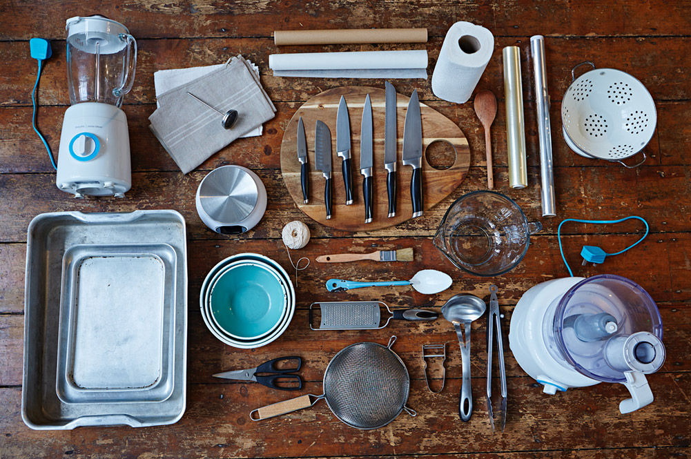 kitchen utensils laying in a flat lay on a wooden table
