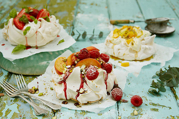 3 different pavlovas with fruit on top and fruit sauce over it