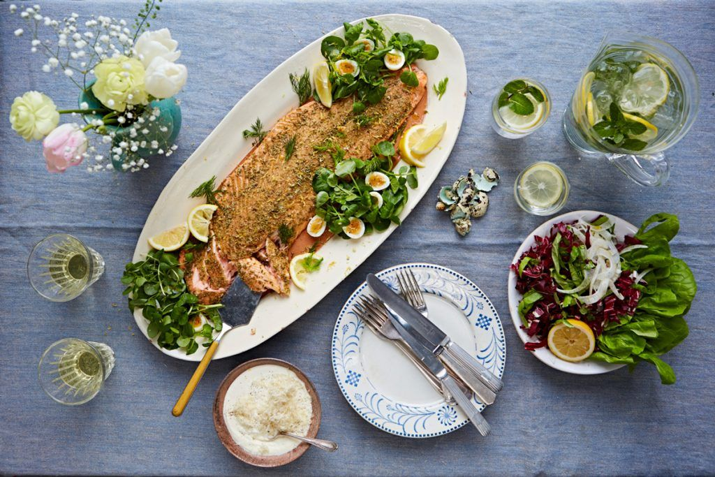 fish supper. baked salmon with slices of lemon and eggs and a side dish of salad