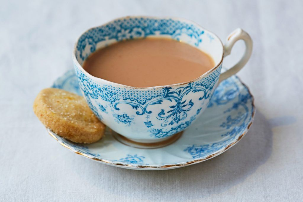 a cup of tea with a biscuit on the side