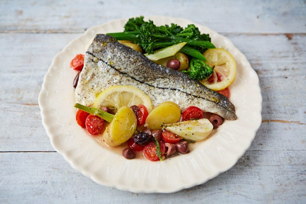 fish on a plate with greens and lemon slices