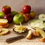 a variety of apples sliced in different ways with different knives