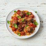 Spaghetti and meatballs in tomato sauce with basil on top