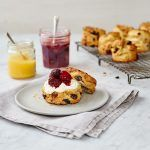freshly baked scones with raisins in and jam and cream on top