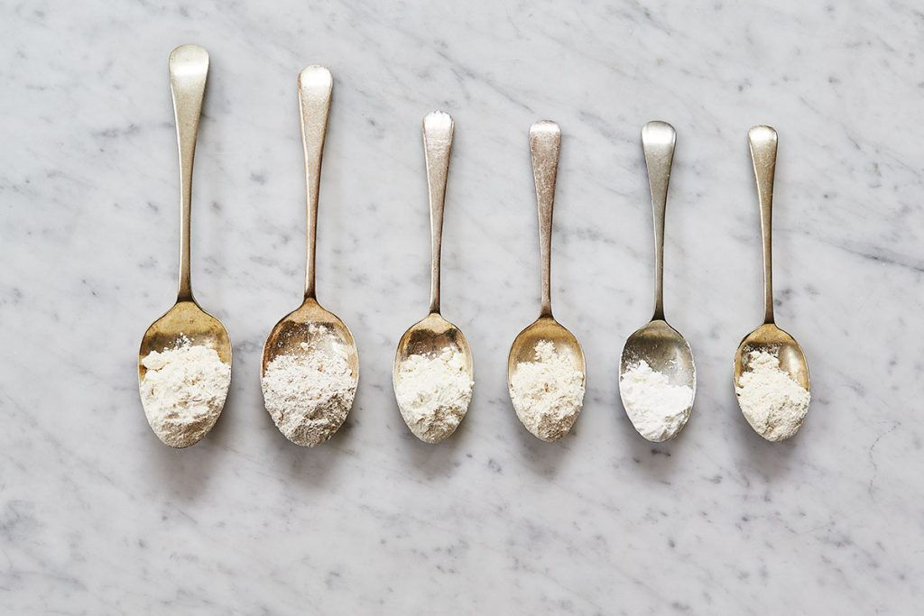 spoons with heaps of flour in a row
