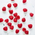 raspberries flat lay scatter on white table