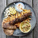 lamb kebabs with chips, pitta bread, sour cream and guacamole