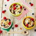 granola and oats breakfast with raspberries and blueberries and yoghurt on top