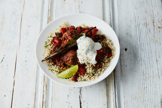 chilli meatballs with rice and yoghurt and herbs on top
